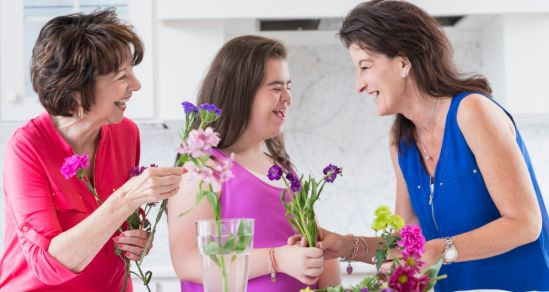 An image of three women of different generations. The youngest is a woman with disability. They are laughing and arranging flowers.