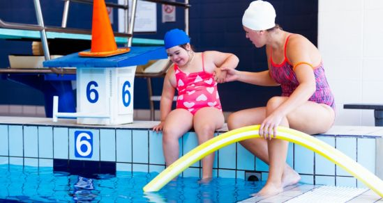 The photograph shows the edge of a swimming pool. There are two people, one a young girl with disability, the other a woman. The woman is holding a pool noodle in one hand, and guiding the girl into the pool with the other. They are next to a diving board with a cone placed on top.