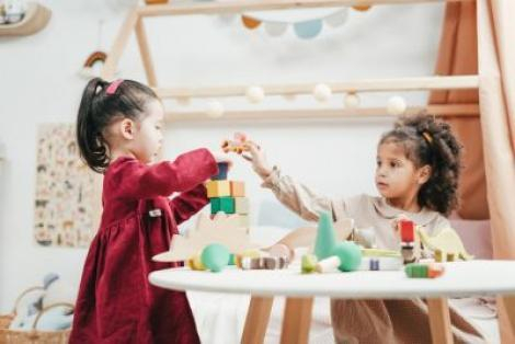 Two girls at a table playing with  wooden blocks