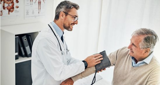 A Doctor wearing white coat and glasses has a stethoscope around his neck. He is holding a blood pressure monitor and wrapping the band around a patients arm in preparation to take blood pressure reading.