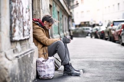 Image of homeless man sitting on a the side of a footpath.