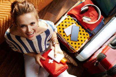 Image of a woman holding a first aid kit, with an open suitcase beside her.