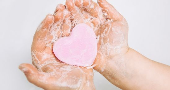 A childs hands holding heart shaped soap.