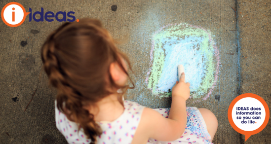 An image of a young girl drawing with chalk on concrete