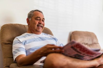 Image of smiling Aboriginal man sitting on a couch with his leg crossed.