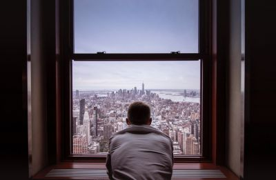 Man in grey shirt looking out window at city buildings