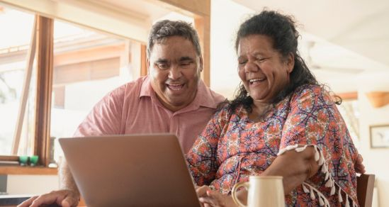 A mature Aboriginal couple sit at a table. In front of them is a laptop, they are both smiling/ laughing at something on the screen. A cup of sits to the left of the woman.