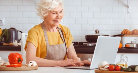 An image of an older woman in a kitchen looking at a laptop. She is wearing an apron and is surrounded by vegetables and cooking utensils