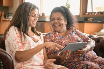Image of smiling elderly woman and younger woman on a couch pointing at a tablet devices screen.