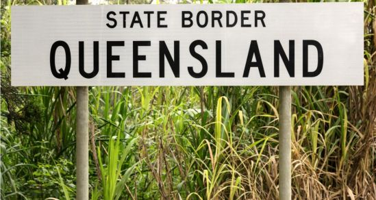 "A photo of a State Border Sign, with the writing ""State Border Queensland"" in black on the white sign."