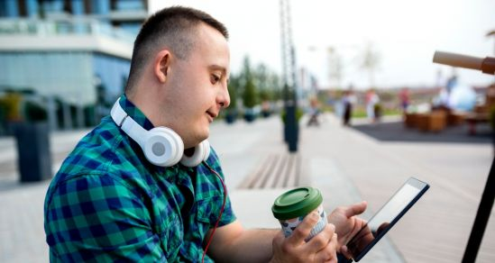 A teen male living with intellectual disabilty, sitting looking at a tablet device, He is holding a reusable takeaway cup and has headphones resting on his neck.of
