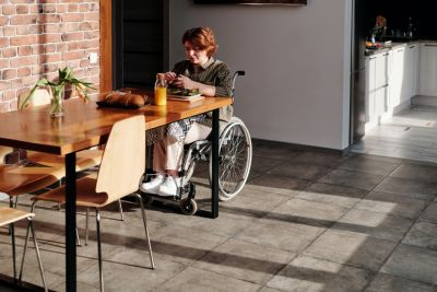 Woman sitting in a wheelchair at a table, preparing a meal.