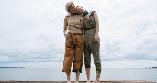 Two women standing together supporting one another. In the background is water and a cloudy sky.