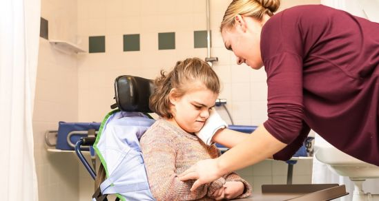A care worker assisting a child with disability
