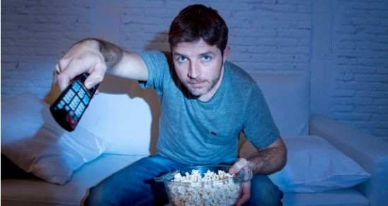 A man holds a remote pointed to the TV, on his lap he has a bowl of popcorn. He is sitting on a lounge in a semi-darkened room. The light from the TV reflects from his face.