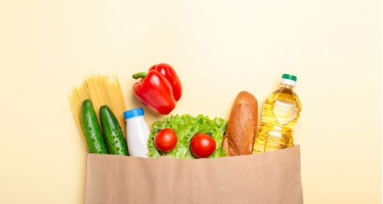 An image of a paper bag with cucumber, pasta, milk, capsicum, lettuce, tomato, bread and oil peeking out of the top. A concept photo of a food hamper.