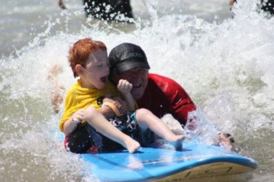 An image of a young boy on a surfboard in the ocean with a volunteer.