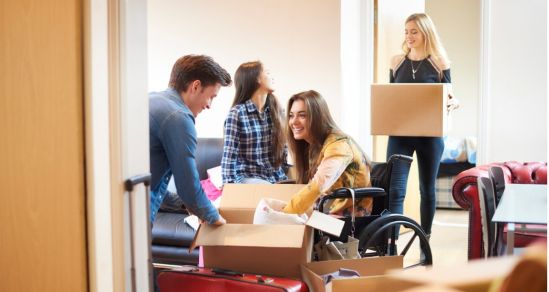 A group of University students are moving into a shared flat. They are surrounded by boxes. One student is in a manual wheelchair.