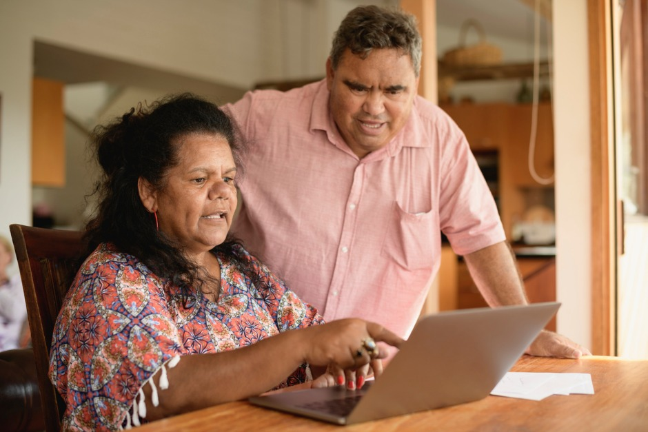 Image of elderly couple looking at a laptop computer inside their home.