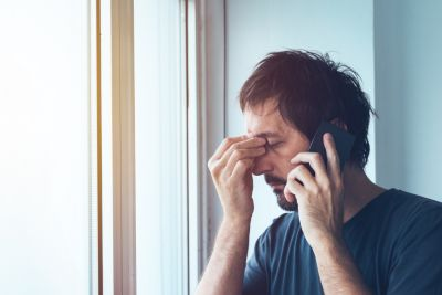Anxious man talking with someone on a mobile phone, he has his hands pinching his forehead.