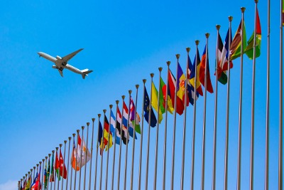 Image of aeroplane flying over row of international flags