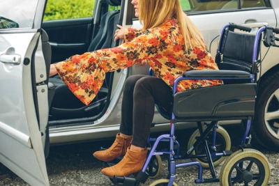 Young woman in a wheelchair getting in a car