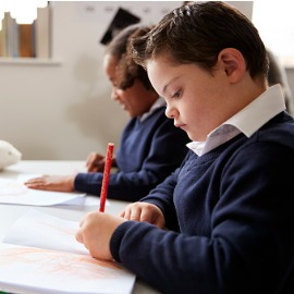 Image of school student who has down syndrome working in a classroom