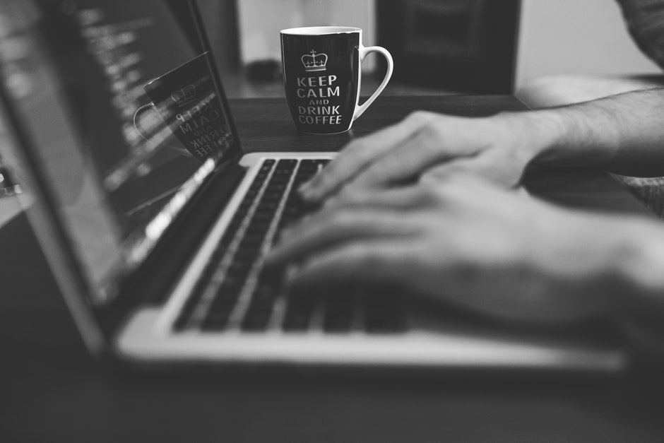 "black and white image of hands typing on a laptop. a mug sits behind and reads ""Keep Calm and Drink Coffee""."