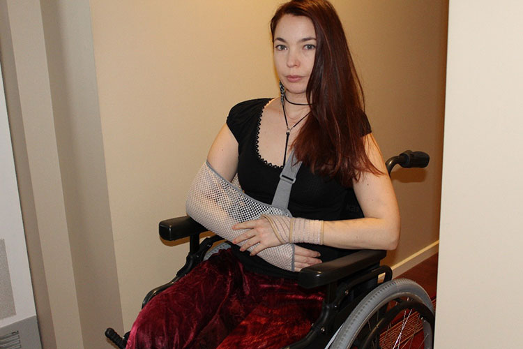 Woman in a wheelchair with her arm in a sling.