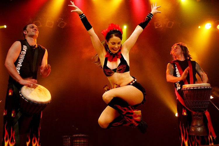 Woman dancing on stage with two drummers. She is wearing a bikini top and black boots with red and yellow flame detailing.