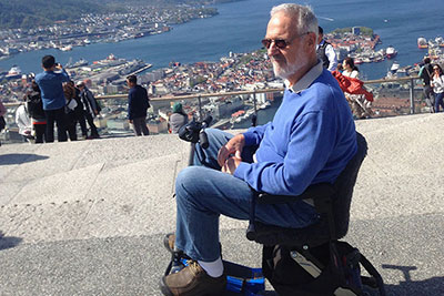 Man sitting in mobility scooter overlooking a beautiful ocean vista