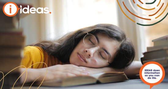 tired woman with glasses sleeping with face on open book. IDEAS logo is in upper left corner.