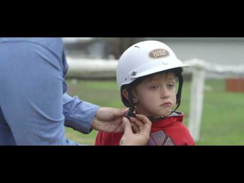Person doing up a child's helmet
