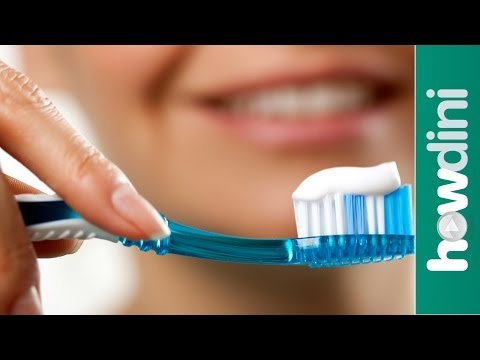 Toothbrush with toothpaste on it with a smiling lady behind it