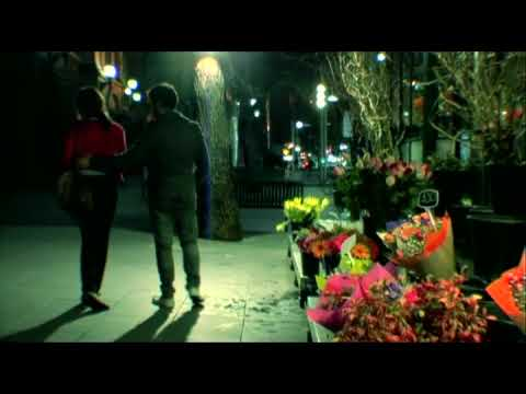 2 people walking down the street past a flower shop