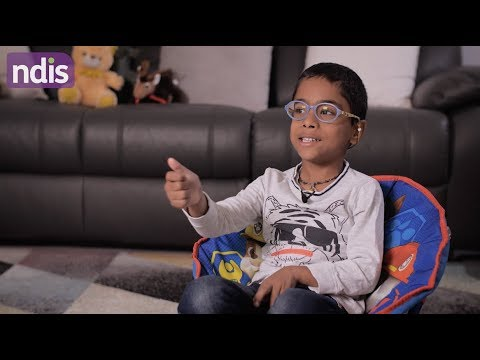 Boy sitting in chair in lounge room talking