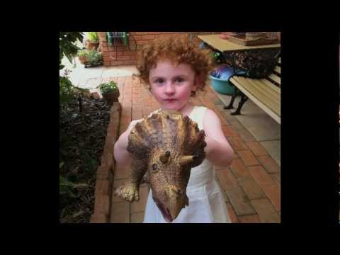 Little girl holding a dinosaur toy