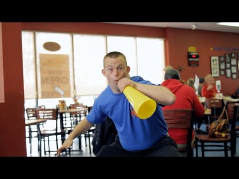 Man standing using a loud speaker in a restaurant