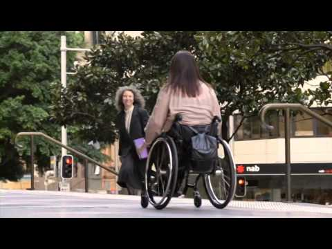 Lady in a wheelchair wheeling down the street
