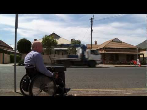 Man sitting on the side of the road in a wheelchair