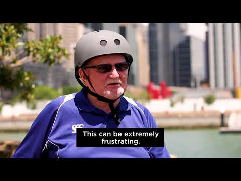 Man sitting in wheelchair with a helmet on with city background speaking