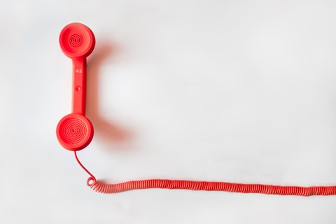 red phone handset with spiral chord