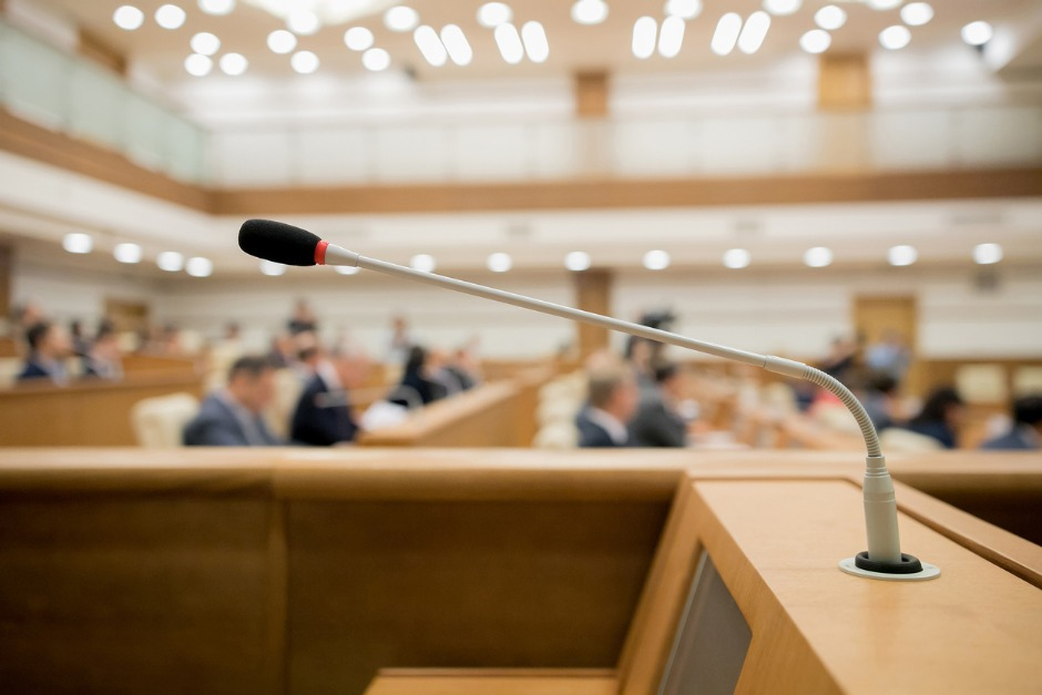 Image of a microphone at a lectern in a formal inquiry chamber