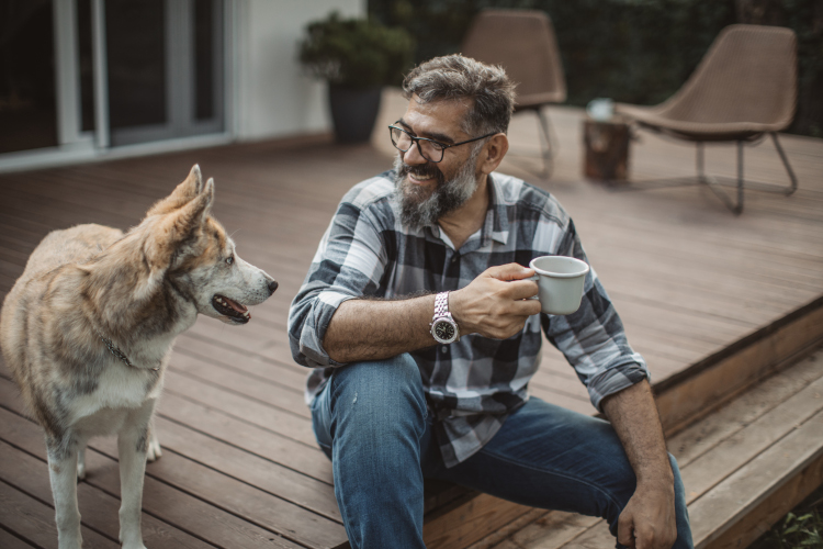Image of a sitting man, holding a cup and looking at a dog.