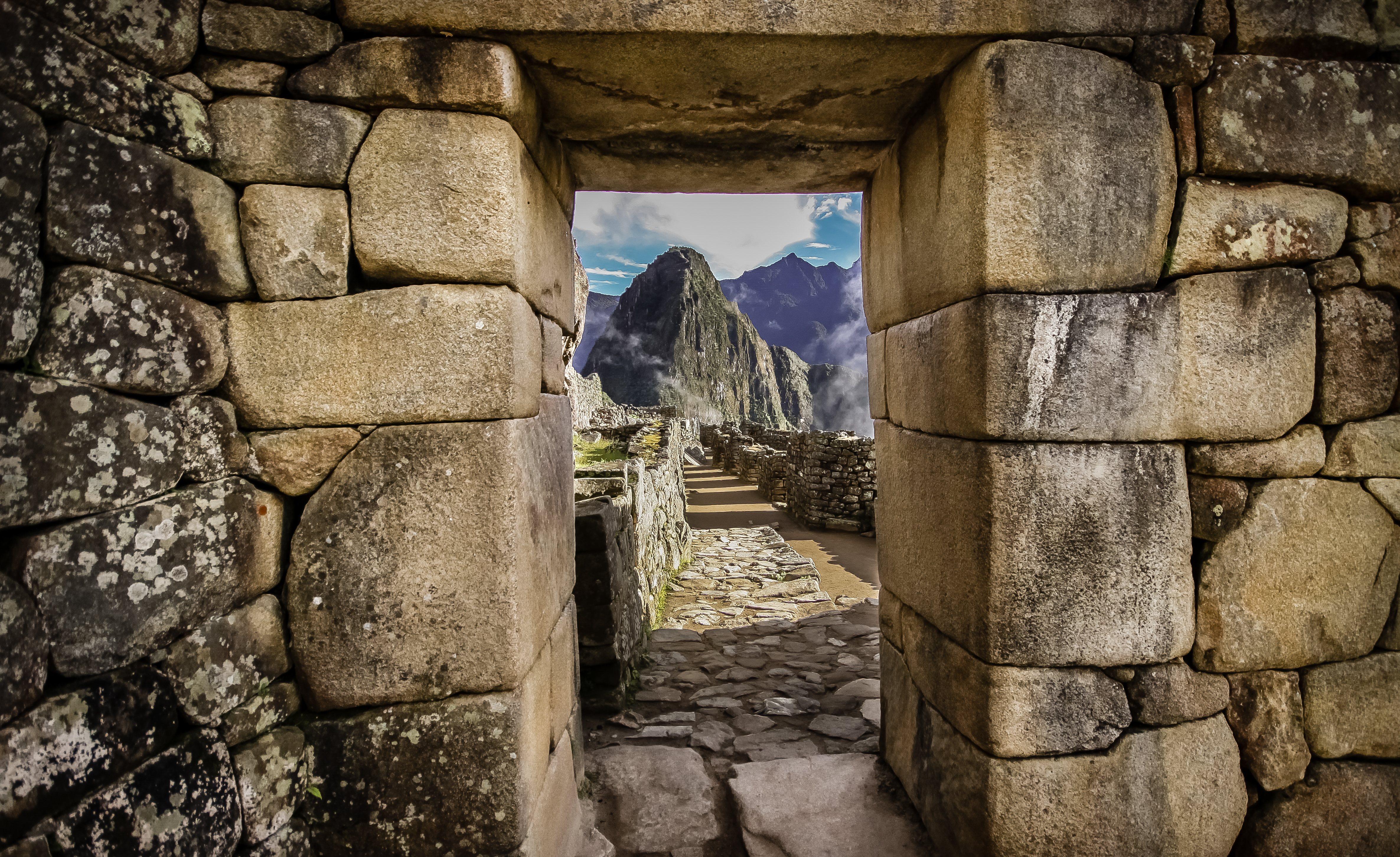 View of mountain peak through window in stone wall