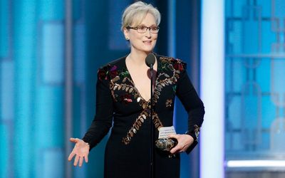 Actor Meryl Streep stands at a podium on stage at the Oscars