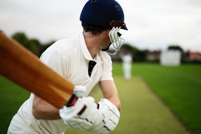 Image of cricket player with bat raised waiting for the ball
