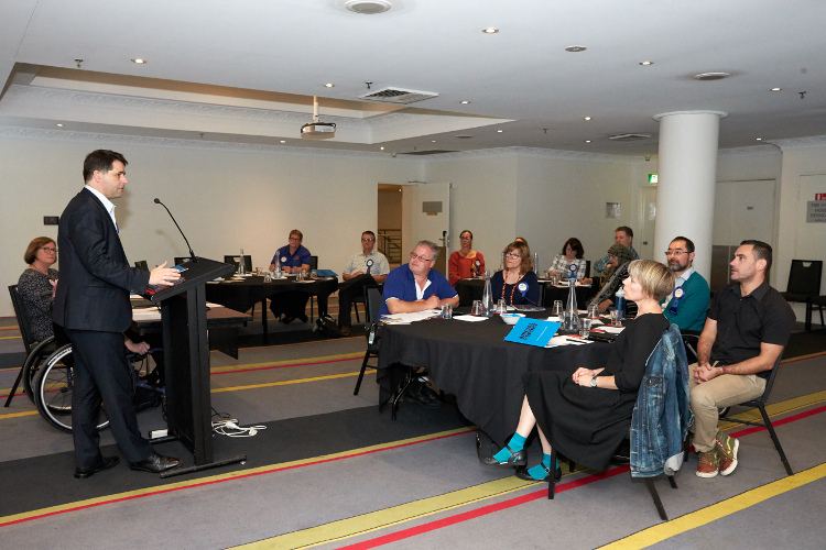 Image of Alastair McEwin speaking at IDEAS AGM with audience looking on
