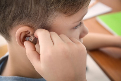 small boy with hearing aid