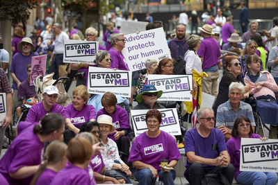 Image of people protesting in purple shirts with placcards